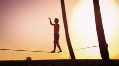 Lens flare shot of a man balancing on the slackline near Venice Beach, Stock Footage