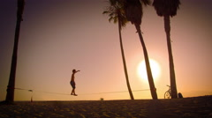 Long distance lens flare shot of a man slacklining near Venice Beach, California Stock Footage