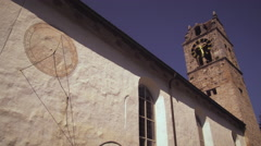 Static shot of an old church with a sundial on its wall in Switzerland Stock Footage