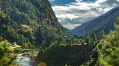 Time-lapse of a Himalayan valley with a river and a small village. Stock Footage