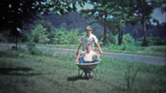 TENNESSEE, USA - 1953: Older brother pushing around kid in a wheelbarrow for Stock Footage