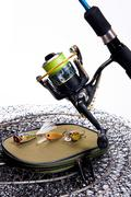 Fishing rod and reel with bag for baits on white. Stock Photos