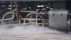 Narrow gauge steam locomotive details of wheels and drives steam during start up Stock Footage