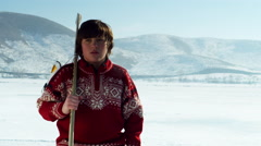 Young boy with a hockey stick walking onto a frozen pond. Stock Footage
