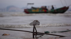 Iron anchor on the beach, fishing boat on the sea Stock Footage