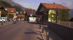 A panning shot following a bycyicle past the Alder de la Gare hotel in Brienz, Stock Footage