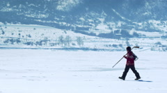 Young person walking through snow with hockey gear. Stock Footage