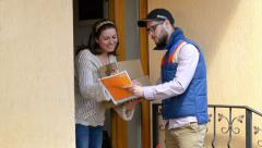 Courier Delivering a Package to a happy woman Stock Footage