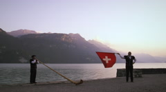 Alphorn player and flag thrower perform near lake Stock Footage