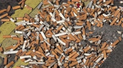 4K Close up smoked cigarette butt tobacco nicotine filter poison stacked harmful - stock footage