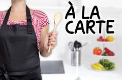 A la carte cook wooden spoon holds background Stock Photos