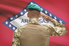 Dark-skinned soldier in hat facing US state flag series - Arkansas - stock photo