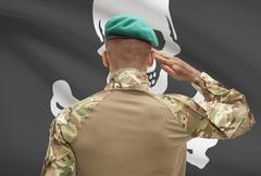 Stock Photo of Dark-skinned soldier in hat facing flag series - Jolly Roger