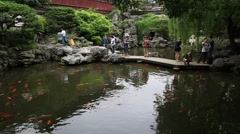 People taking pictures at the pond of Yuyan garden in Shanghai Stock Footage