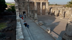 Time lapse of tour groups sitting and moving around synagogue ruins Stock Footage