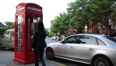 Young asian woman entering into a red typical English style phone box of Thames Stock Footage