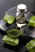 Sliced aloe leaves with oil on the stone - stock photo