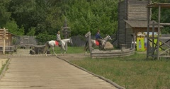Stock Video Footage of Three Riders, Horsemen, Are Riding by Ancient City Road, Museum, Park