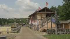 Observation Building With a Flags Near Sandy Stadium, People Distantly Stock Footage
