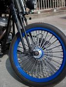 Chrome motorcycle front wheel and fork, with blue alloy rim - stock photo