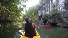 Old man paddles on kayak and looks upward at cliff Stock Footage