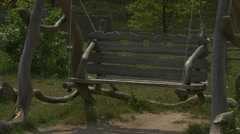 Wooden Log Swing Is Swinging, Slow Motion, Green Trees on Background Stock Footage