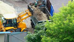 25 Tons Excavator loading truck with sand. Cernihiv city, Ukraine. Stock Footage