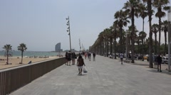 People walking on Barceloneta Palm road in Barcelona city Stock Footage