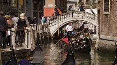 VENICE, ITALY - May 2:  Gondolier steer's gondola under a bridge on May 2, 2012 Stock Footage