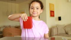 Smiling girl insert coins into money saving box Stock Footage