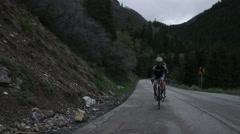 Couple road biking through mountains Stock Footage