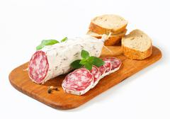 French Saucisson Sec and sliced crispy roll on cutting board Stock Photos