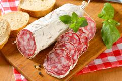 French Saucisson Sec and sliced crispy roll on cutting board - stock photo