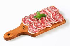 Sliced French Saucisson Sec on cutting board - stock photo