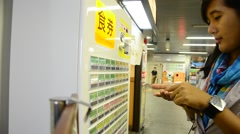 Thai woman buying ramen from Vending Machine at Noodle Shop of train station Stock Footage