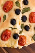 Focaccia with black olives, tomatoes and basil - stock photo