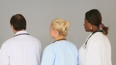 Doctors turning around to look and smile at the camera - stock footage