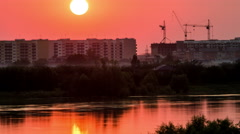 Sunset over a city being construction built. River or lake. 4k timelapse Stock Footage