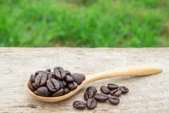Coffee beans in wooden spoon on wooden background - stock photo