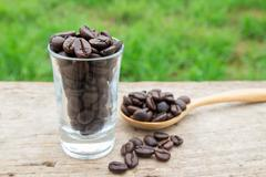 Coffee beans in glass on wooden background Stock Photos
