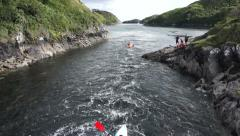 Drone flys over kayaks on Irish river rapids - stock footage