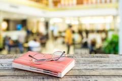 Notebook and eyeglasses on wooden table with blur background Stock Photos