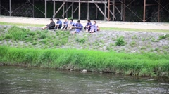 Japanese people sit and talk at riverside of Kamo River in Kyoto, Japan Stock Footage