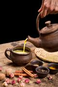 Pouring masala tea from pot - stock photo