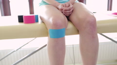 Knee kinesiotaping, physical therapist taping patient knee Stock Footage