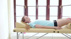 physical therapist inspecting injured knee of young woman - stock footage