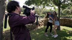 Man shooting videoclip of girls dancing in park with professional camera Stock Footage