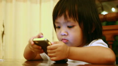 Asian baby to looking and play mobile phone Stock Footage