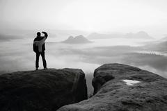 Moment of loneliness. Man on the rock empires  and watch over the misty and f Stock Photos