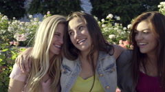 Friends Sit, Arms Around Each Other, On A Wall In A Rose Garden And Smile (4K) Stock Footage